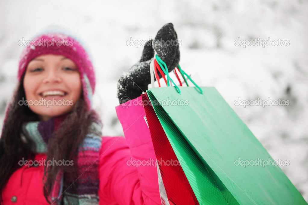 Winter girl with gift bags on snow background — Stock Photo #6934948