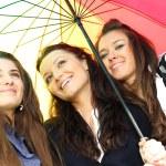 Smiling girlfriends under umbrella — Stock Photo #7078455
