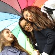 Smiling girlfriends under umbrella — Stock Photo #7078469