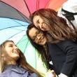 Smiling girlfriends under umbrella — Stock Photo
