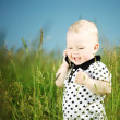 Boy in grass call by phone - Stock Photo