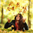 Woman drop leaves in autumn park — Stock Photo #7192930