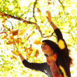 Woman drop leaves in autumn park - Stock Photo