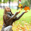 Woman drop leaves in autumn park — Stock Photo #7192997