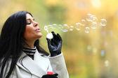 Autumn woman blow bubbles — Stock Photo