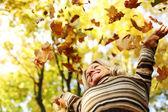 Kobieta kropla liści w parku jesień — Zdjęcie stockowe