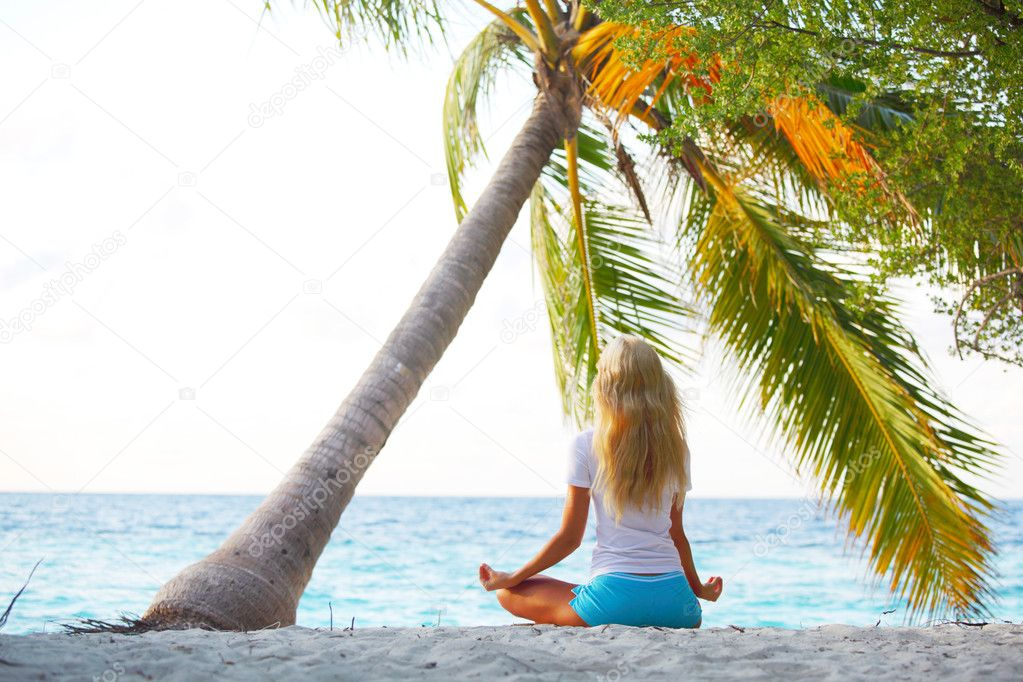 Yoga woman on sea coast under palm — Stock Photo #7203697