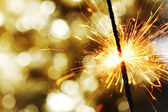Sparkler on bokeh background — Stock Photo