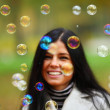 Autumn woman blow bubbles - Stock Photo