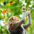 Woman drop leaves in autumn park — Stock Photo #7294466