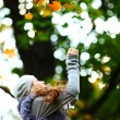 Woman drop leaves in autumn park — Stock Photo #7294475