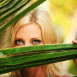 Woman behind the palm leaves — Stock Photo #7331983