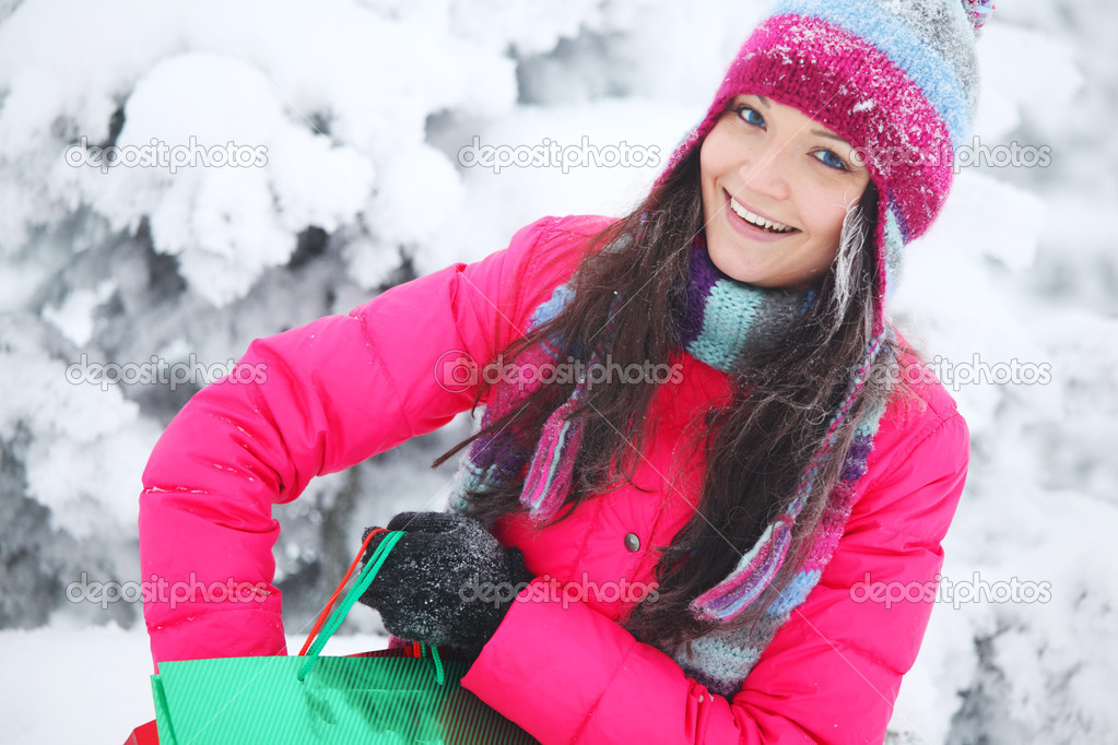 Winter girl with gift bags on snow background — Stock Photo #7473271
