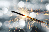 Sparkler on bokeh background — Stock Photo