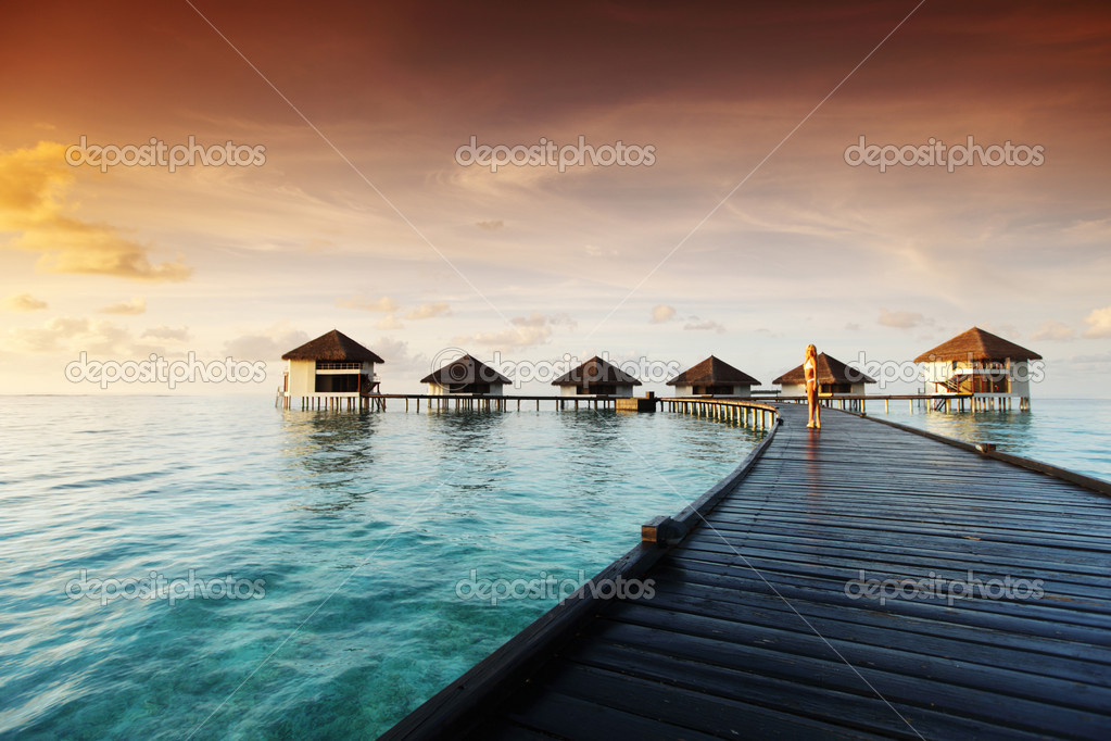 Woman in a dress on a bridge home sea and the maldivian sunset on the background — Stock Photo #7941802