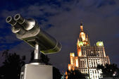 Observation telescope at a dark sky looks at a tall building — Stock Photo