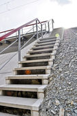 Concrete staircase with a metal handrail on the gravel embankment — Stock Photo