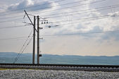 Railroad track, embankment, and power poles — Stock Photo
