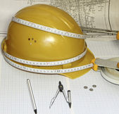 A helmet, a roulette and compasses against the drawing — Stock Photo