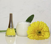 Nail polish a cream and a yellow flower — Stock Photo