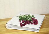 Foto albumet med en bukett blommor på ett träbord — Stockfoto