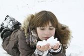 The beautiful girl lays with snow in hands — Stock Photo