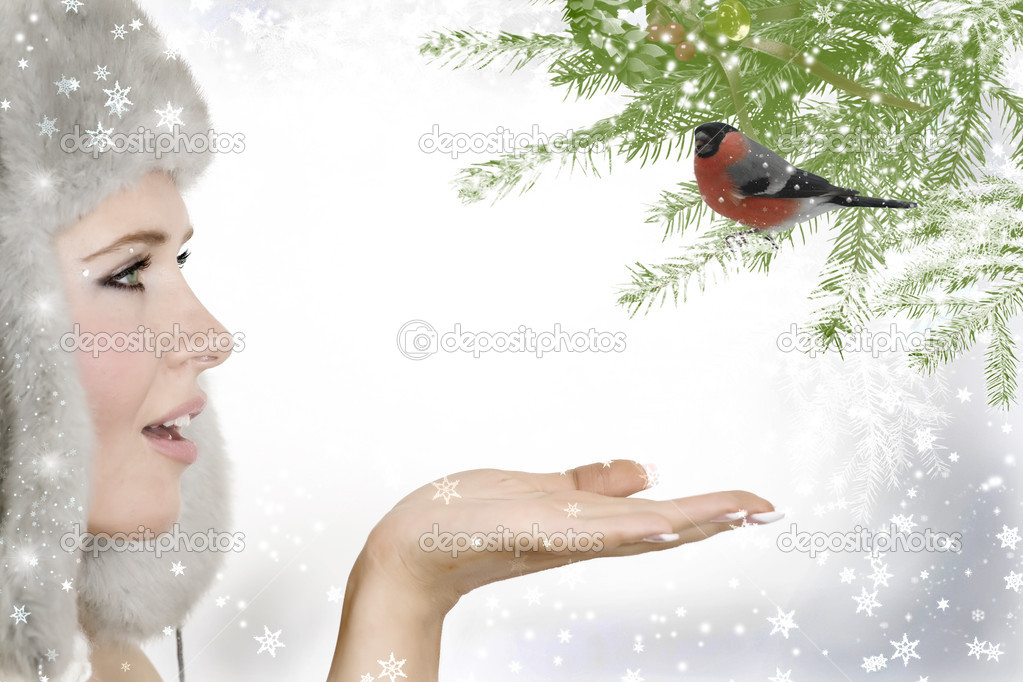 Close up portrait  of a beautiful girl in a fur hat looking at bullfinch sitting on a christmas tree brunch — Stock Photo #7019985