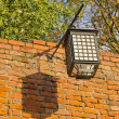Ancient illuminator mounted on red brick wall. Oldtown details. — Stock Photo