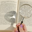 Woman's hand holding magnifying glass over germbook page. — Stock Photo #7425150