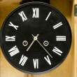 Stockfoto: Ancient black clock with romnumbers and arrows.