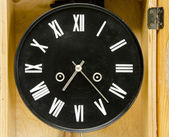 Ancient black clock with roman numbers and arrows. — Stock Photo