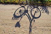 Standing bicycle shadow on gravel road. — Stock Photo