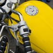 Stock Photo: Motorcycle wheel and yellow petrol tank details.