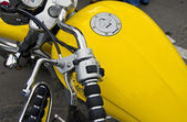 Motorcycle wheel and yellow petrol tank details. — Stock Photo