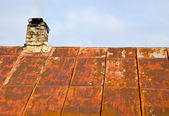 Rusty roof tin and ramshackle brick chimney. — Stock Photo