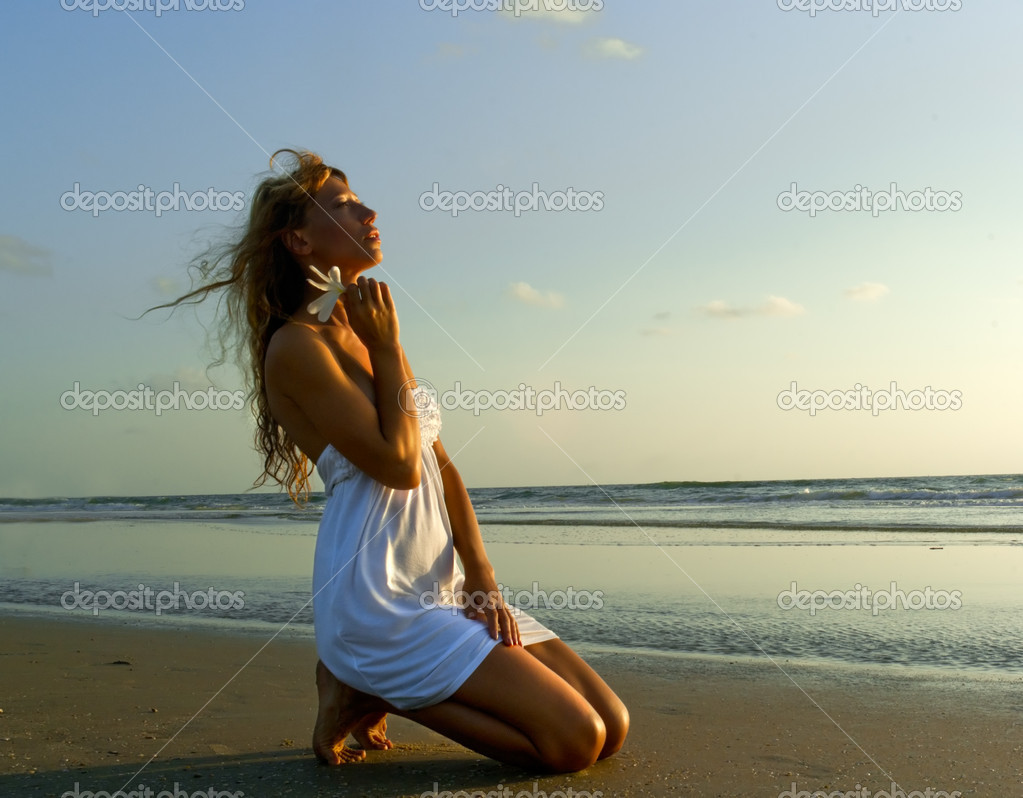 Gorgeous woman in white dress kneel on the beach on sunset — Stock Photo #7855152