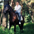 Groom posing on horse in forest — Stock Photo #7041110