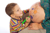 Smiling little son painting the belly of his pregnant mother — Stock Photo