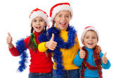 Three children in Santa hats with thumb up sign — Stock Photo
