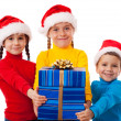 Three smiling kids with Christmas gift — Stock Photo #7510182