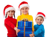 Three smiling kids with Christmas gift — Stok fotoğraf