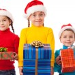 Three smiling kids with Christmas gift boxes — Stock Photo