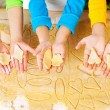Child's hands with dough over the table — Stock Photo