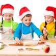 Three smiling kids with Christmas cooking — Stock Photo