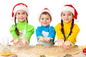 Three smiling kids showing Christmas cooking — Stock Photo