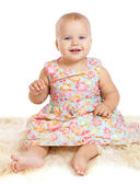 Smiling baby sitting on the furry rug — Stock Photo