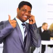 Afro-American businessman talking on mobile phone with his team in the back — Stock Photo
