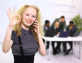 Closeup of beautiful young woman speaking on cell phone with team in backgr — Stock Photo