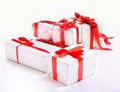 Kırmızı hediye kutuları yığını üzerinde beyaz izole yay ile dekore edilmiş — Stok fotoğraf