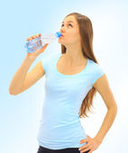 A beautiful young woman to drink the water on a blue background — Stock Photo